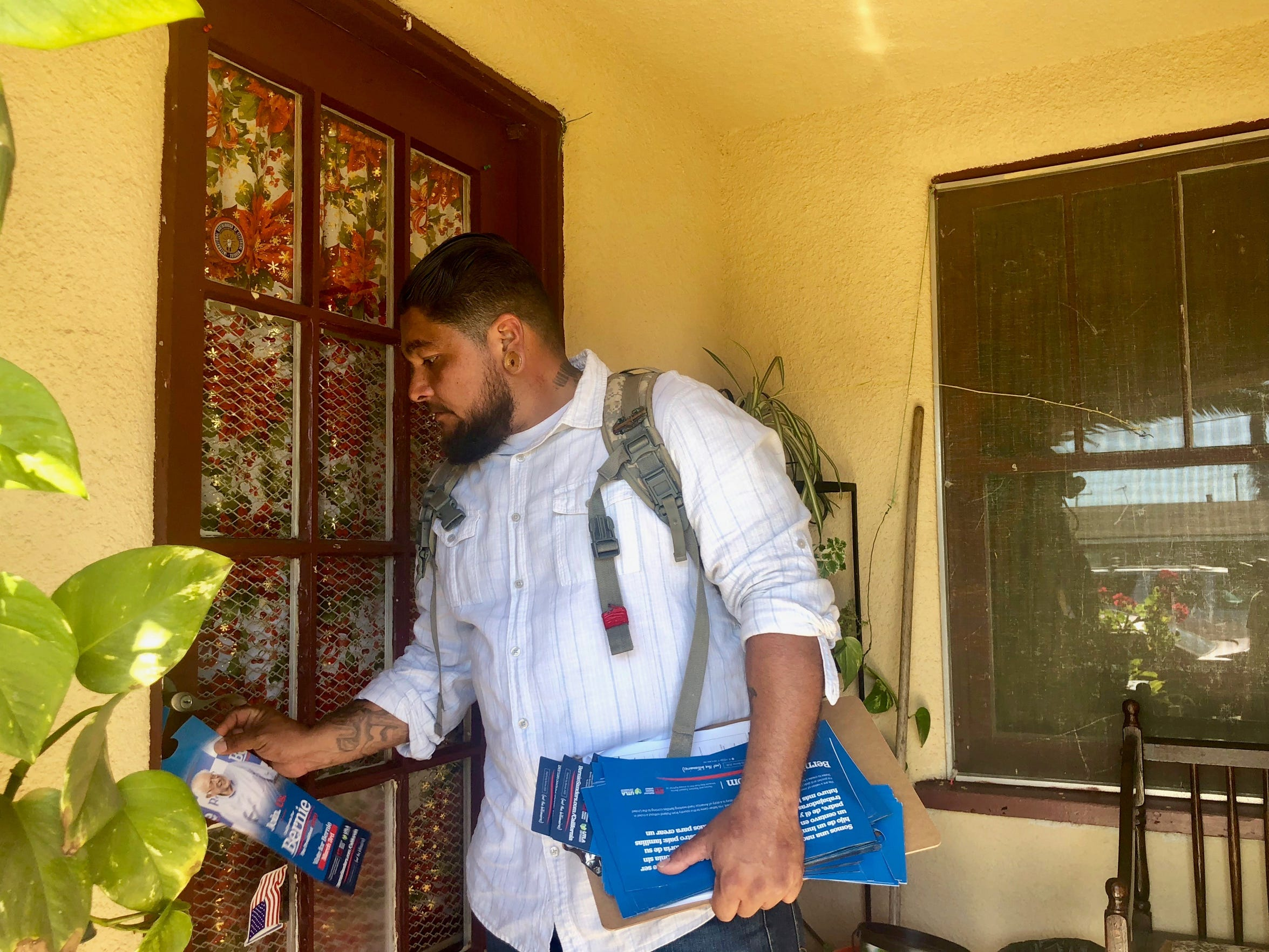 Volunteer Antonio Sepulveda leaves a flier for presidential candidate Bernie Sanders at a home in Oxnard's La Colonia neighborhood on Feb. 1. With Latino outreach a priority for Sanders, the campaign has opened an Oxnard office.