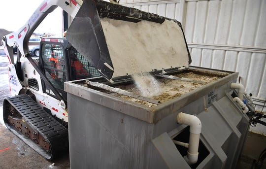 Texas Department of Transportation inspector Kane Eavenson adds salt to a brine-making vat. TxDoT sprays brine on the roadways to prevent freezing.