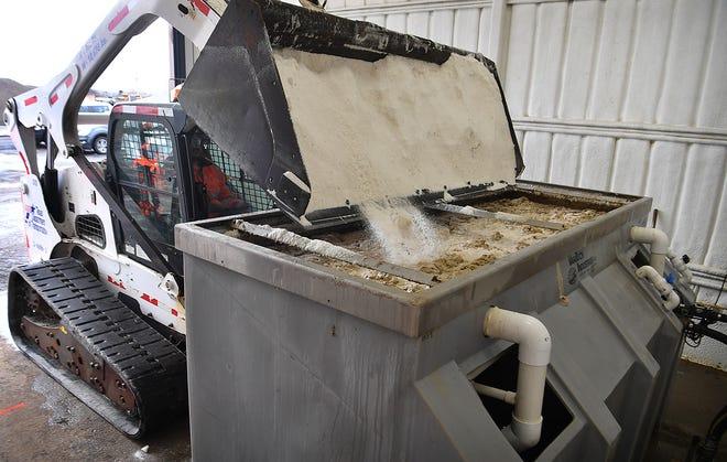 Texas Department of Transportation inspector Kane Eavenson adds salt to a brine-making vat. TxDoT sprays brine on the roadways to prevent freezing.
