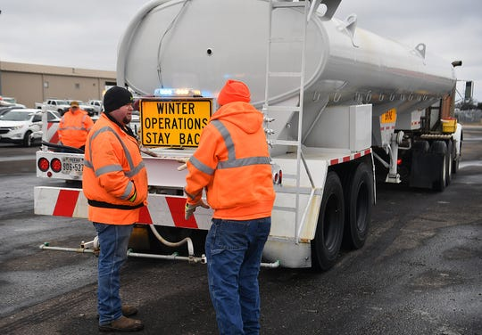 Anthony McCormick, left, and Andy Pruett, operations specialists for the Texas Department of Transportation, check their brine-spraying tanker before heading out to treat area roadways.