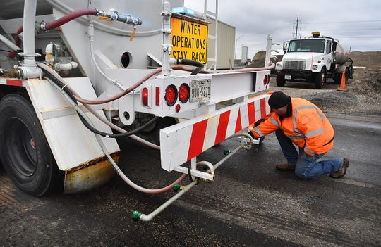 Anthony McCormick of the Texas Department of Transportation checks the spray nozzles on a brine tanker before heading out to treat area roadways ahead of an approaching winter storm.