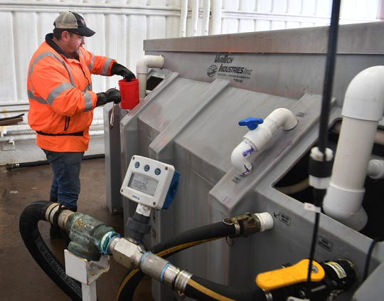 Kane Eavenson, an inspector for the Texas Department of Transportation, prepares to take a salinity reading on a batch of brine that will be used to treat area roadways to prevent freezing.