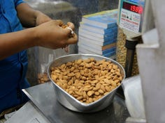 In this June 22, 2019 file photo, a shopkeeper weighs California almonds for a customer at a shop in New Delhi, India. Almonds used to have about 170 calories per serving, then researchers said it was really more like 130. A little later, they said the nuts may have even less.  The shifting numbers for almonds show how the figures stamped on nutrition labels may not be as precise as they seem. (AP Photo/Altaf Qadri)
