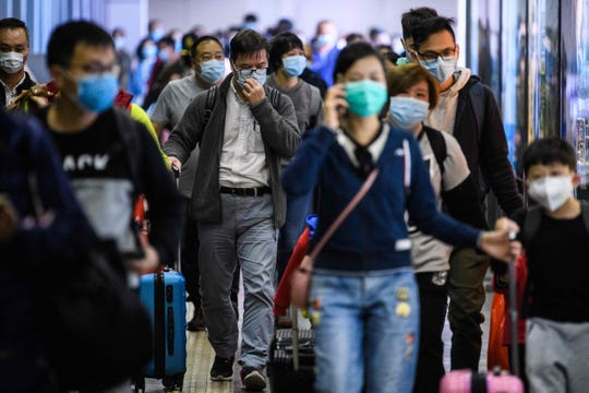 Passengers wear protective face masks as they arrive from Shenzhen to Hong Kong at Lo Wu MTR station, hours before the closing of the Lo Wu border crossing in Hong Kong, on Feb.3, 2020, amid an outbreak of a coronavirus which began in the Chinese city of Wuhan. Hong Kong announced it was closing all but two land crossings with the Chinese mainland on February 3 to slow the spread of a deadly new coronavirus as medics staged strikes calling for the border to be completely sealed.