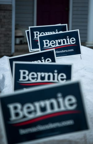 Six Bernie Sanders signs line a driveway before the Democratic presidential caucus on Monday, Feb. 3, 2020 in Larchwood, Iowa.