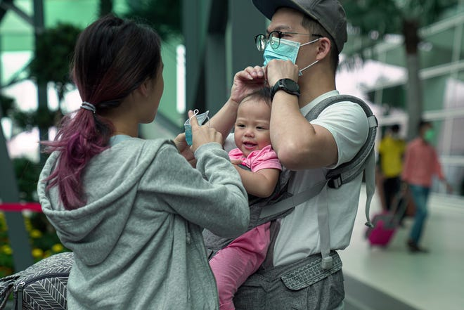 A family adjust their masks at the Kuala Lumpur International Airport 2 in Malaysia.  Thailand is at great risk for spreading the virus due to the influx of travelers from mainland China. Thailand has confirmed one of the first human to human transmissions of the coronavirus outside of China.