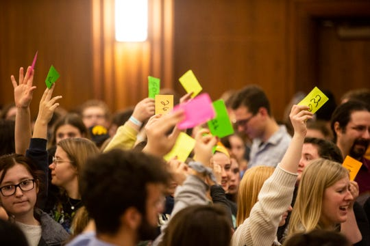 University of Iowa students hold up numbered cards while they caucus on Feb. 3, 2020, in Iowa City.