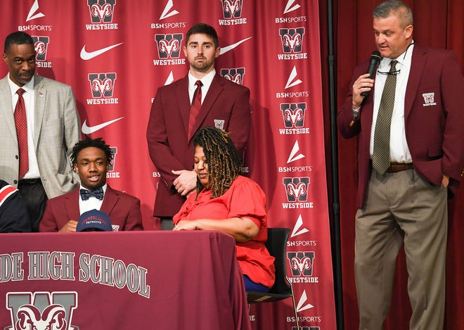 Coach Scott Earley speaks, right, near Shedrick Junior Smith, who signed a National Letter of Intent to play football at Cumberland College , during a ceremony at Westside High School in Anderson Wednesday, February 5, 2020.