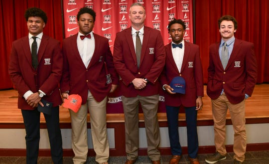 Elijah Harper(Charleston Southern University), left, Nigajuan Mansell (Mercer), Coach Scott Earley, Junior Smith(Cumberland College), and Blair Garner(Charleston Southern) during National Letter of Intent signing day at Westside High School in Anderson Wednesday, February 5, 2020.