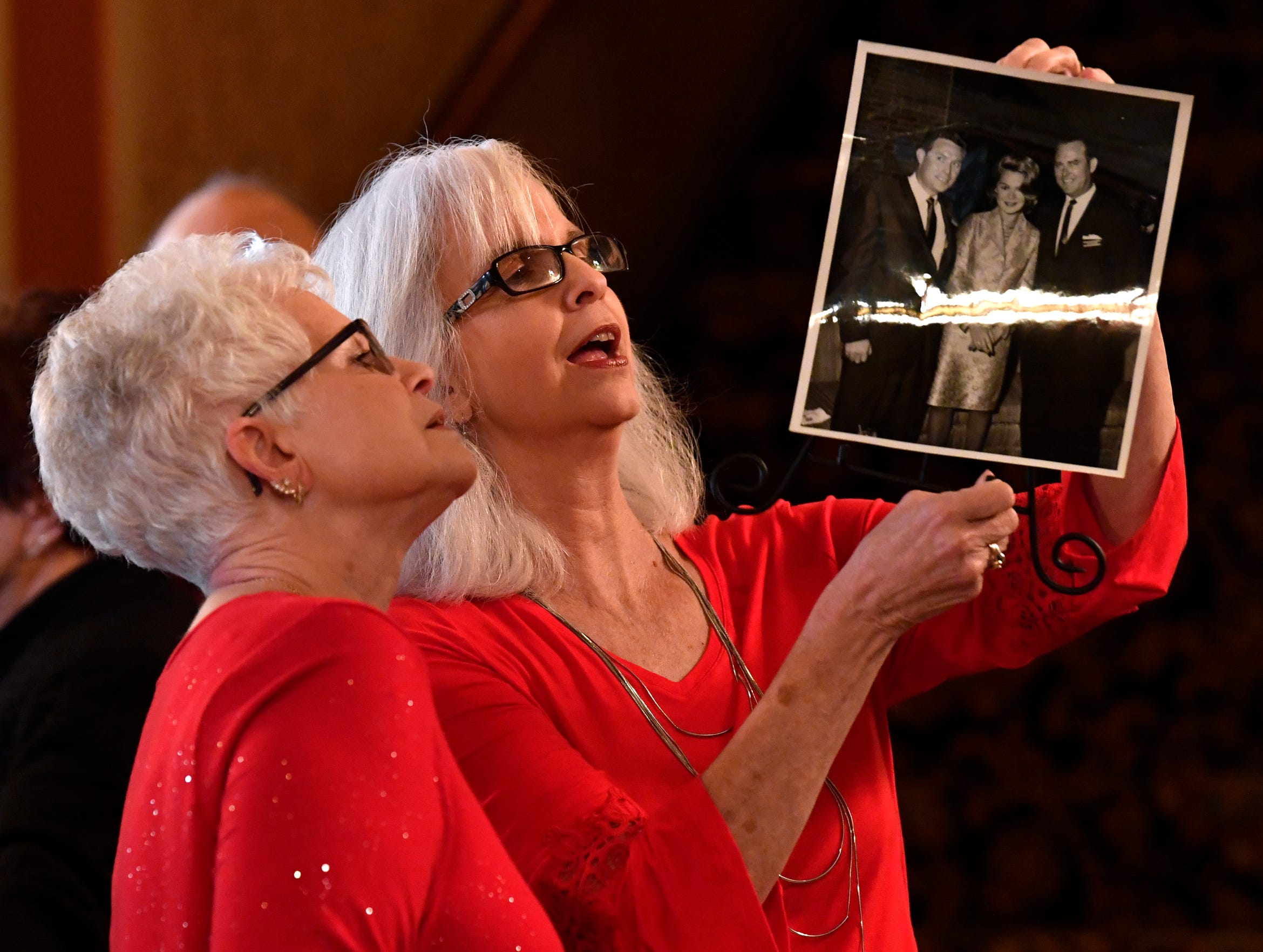 Sisters Regina Windland (left) and Benje Campbell study the back of a photograph showing Frank Sheffield with movie stars Sandra Dee and James Stewart, during a party for Sheffield at the Paramount Theatre Jan. 31.