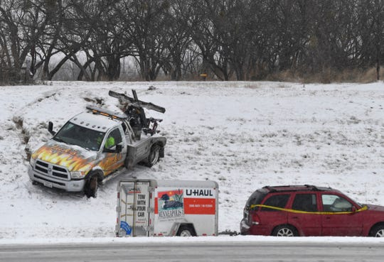 A tow truck slides down the embankment on Interstate 20 Wednesday between Loop 322 and Ambler Avenue Feb. 5, 2020. The driver was guiding the truck down to tow the car below.