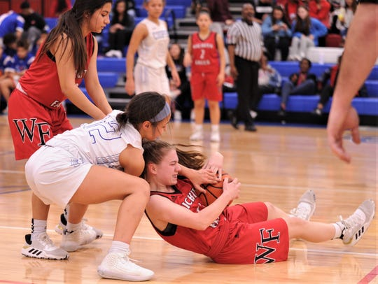 Cooper's Aziah Joe, center, fights Wichita Falls High's Kristal Marzett for a loose ball. Cooper beat the Lady Coyotes 64-16 in the District 4-5A game Tuesday, Feb. 4 at Cougar Gym.