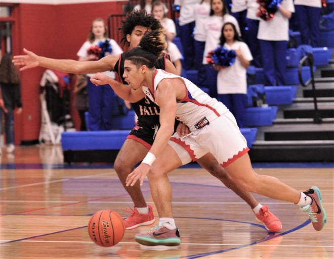 Cooper's Noah Garcia, right, drives past a Wichita Falls High defender in the first quarter. Cooper beat the Coyotes 69-51 in the District 4-5A game Tuesday at Cougar Gym.