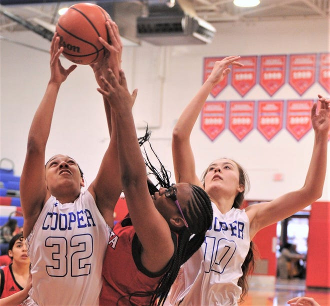 Cooper's Jennika Willis (32) and Brianna Garcia (10) battle Wichita Falls High's Jordyn Green for a rebound in the first quarter. Cooper beat the Lady Coyotes 64-16 in the District 4-5A game Tuesday at Cougar Gym.