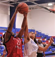 Cooper's Keiana Kemp, right, battles Wichita Falls High's Jordyn Green for a rebound in the first quarter. ​Cooper beat the Lady Coyotes 64-16 in the District 4-5A game Tuesday at Cougar Gym. ​