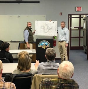 Civil engineer Mark Brooks, left, and developer George DeLoache, show a site plan for 80 town home apartments DeLoache hopes to build off Overlook Road in Arden. About 60 people attended a meeting for neighbors at the Skyland Volunteer Fire Department on Feb. 4, 2020.