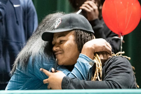 Reynolds senior Don Mosley gets a hug from his mother, Anea Copney, after signing a letter of intent to play junior college football at Ramah in South Carolina during a ceremony at Reynolds High School on Feb. 5, 2020.