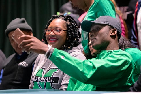 Reynolds senior Jhari Patterson takes a selfie with his mother, Crystal Shaw, before he signed a letter of intent to play college football at Marshall University during a ceremony at Reynolds High School on Feb. 5, 2020.