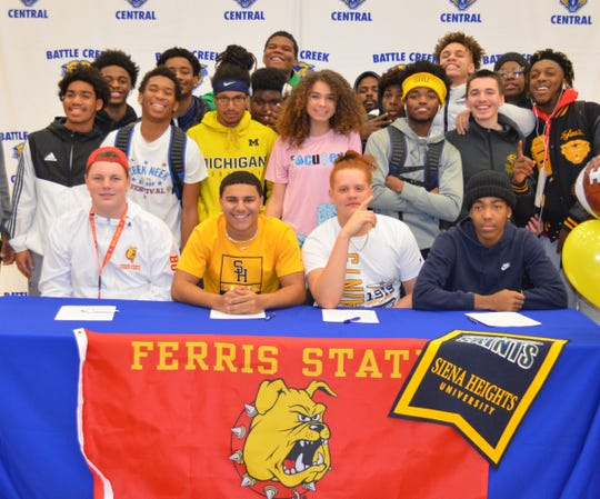 Joined by their teammates, Battle Creek Central had four players pledge to colleges on National Signing Day, including, from left, Kyler Granger, Markel Main, Xavier Hall and Theo Shepherd.