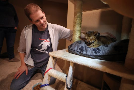 Patrick Moe pets Helix, the family's 5-year-old Abyssinian cat, at their home in Port Orchard on Tuesday, Feb. 4, 2020. Helix, who had been missing since April 2016, was found and turned into the Kitsap Humane Society in late January where he was then reunited with the Moe family.