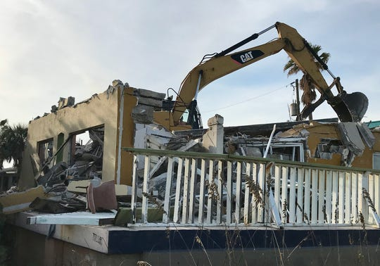 An excavator tears down the three-story Beach House Motel building Tuesday afternoon that faced the Atlantic Ocean.
