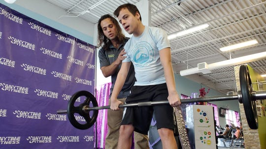 Duquette practices his dead lift with trainer Joe Luther coaching at Anytime Fitness in Palm Bay.
