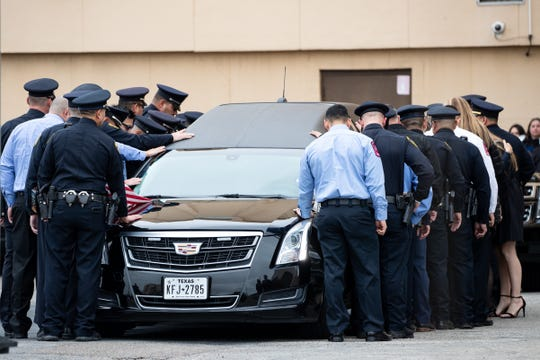 Corpus Christi first responders gather around the hearse carrying officer Alan McCollum outside police department headquarters during the procession to Church Unlimited on Wednesday, Feb. 5, 2020.