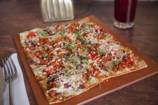 A plant-based spicy 'chorizo' flatbread comes with bell pepper, kalamata olive, micro basil, topped with vegan mozzarella at Harvest Seasonal Grill & Wine Bar.