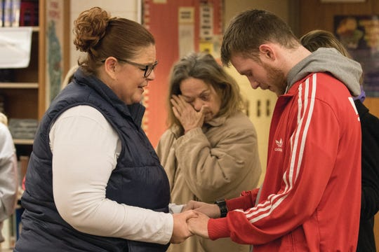 Wanda Gay from Zane Trace prays with Brandon and Jacob Smith's brother Zac Ezelle Wednesday evening during a vigil at Zane Trace High School.