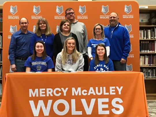 Mercy McAuley students signed National Letters of Intent Feb. 5 to play college athletics. Along with their parents, they are, from left: Lani Hinton (Thomas More University cross country), with Jeffrey & Kathleen; Maddie Dougoud (Capital University basketball) with Christopher & Laura; and Dani Carle, (Thomas More University bowling) with JP & Liesa.  Send more Signing Day photos to mlaughman@enquirer.com.