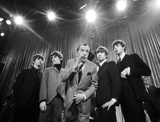 """Ed Sullivan, center, stands with The Beatles during a rehearsal for the British group's first American appearance, on the """"Ed Sullivan Show,"""" in New York on Feb. 9, 1964. From left: Ringo Starr, George Harrison, Sullivan, John Lennon and Paul McCartney."""