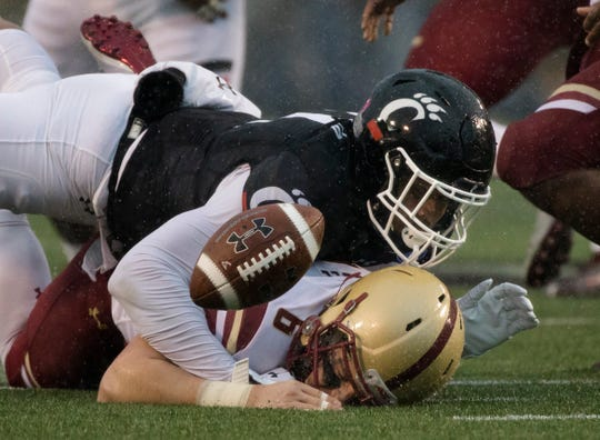 Cincinnati Bearcats linebacker Bryan Wright (11) tackles Boston College Eagles quarterback Dennis Grosel (6) as he fumbles the ball in the first half of the Birmingham Bowl between Cincinnati Bearcats and Boston College Eagles on Thursday, Jan. 2, 2020, at Legion Field in Birmingham, Ala.