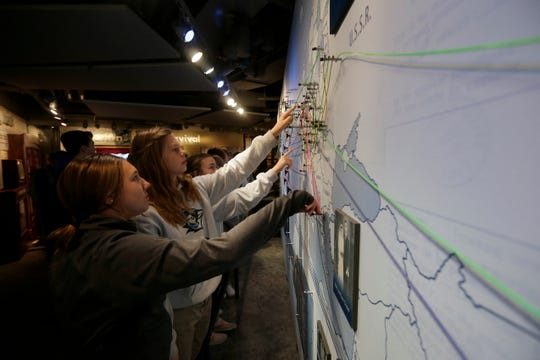 Students trace the lines showing paths of migration taken by Jewish refugees of the Holocaust on a map at the Holocaust & Humanity Center inside the Cincinnati Museum Center on Wednesday, Feb. 5, 2020.