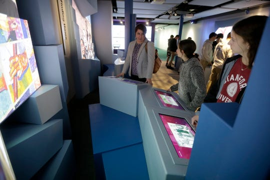Melissa Kevill, eighth grade teacher at St. Joseph School in Cold Springs, Kentucky., talks with her students over an interactive display at the Holocaust & Humanity Center inside the Cincinnati Museum Center in Queensgate on Wednesday, Feb. 5, 2020.