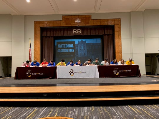 Roger Bacon athletes who signed letters of intent to play college sports were, from left: James Thompson Jr. (University of Wisconsin football), Nolan Tebbe (Thomas More University football), Ryan Lally (Denison University football), Ryan Blaut (Thomas More football), Lyric Harris (Long Island University basketball), Kelly Brenner (Thomas More basketball), Karly Niesen (Urbana University volleyball), Dillon Fischer (Earlham baseball), Evan Kelsey (Wilmington baseball), Jake Brookbank (Wilmington College baseball), Taylor Stahl (Thomas More soccer), Lindsay Ballinger (Thomas More soccer), Arrington Walker (Northern Kentucky University softball).