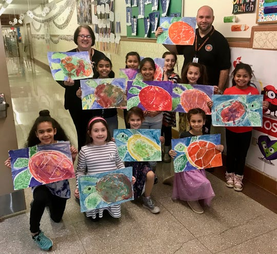 A group of third-graders from School No. 10 in Linden are hosting a dance on March 20 to raise money to help sea turtles after learning they are threatened by marine pollution. The students are pictured with teacher Fran Czylek and Principal David Walker. Front row: Camille Sheridan, Olivia Ciesla, Kali Diaz, Brielle Suros, and back row, Vithoria DaSilva, Gianna Cedeno, Melanie Velarde, Abigail Avila, Mikaela Diaz, and Maia Alvarez. They are holding pictures of turtles drawn by themselves and other students in art class.