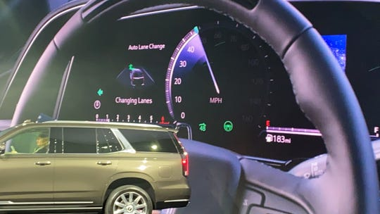 Graphics illustrate the Escalade's lane change on demand hands-free driving feature.
