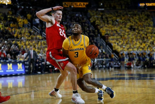 Michigan guard Zavier Simpson drives on Ohio State forward Kyle Young in the second half in Ann Arbor, Tuesday, Feb. 4, 2020.
