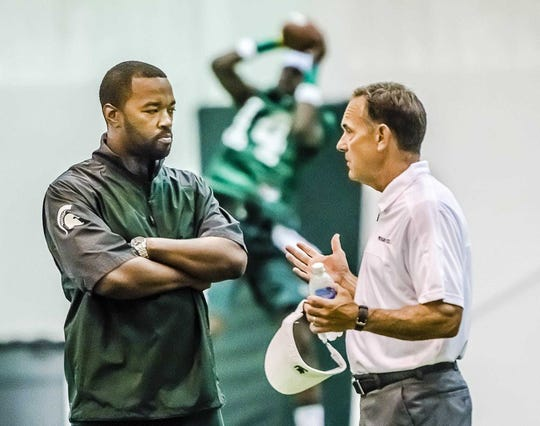 Curtis Blackwell, left, MSU director of college advancement and performance speaks with MSU head coach Mark Dantonio during Day 1 of preseason camp Aug. 3, 2013 in East Lansing. Blackwell's contract was not renewed after expiring May 31, 2017.