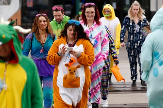 People in dinosaur onesies and other outfits leave O'Tooles and Fifth Avenue bar for other locations during the fourth annual Onesie Bar Crawl at various bars in Royal Oak, Michigan on Saturday, Jan. 25, 2020.