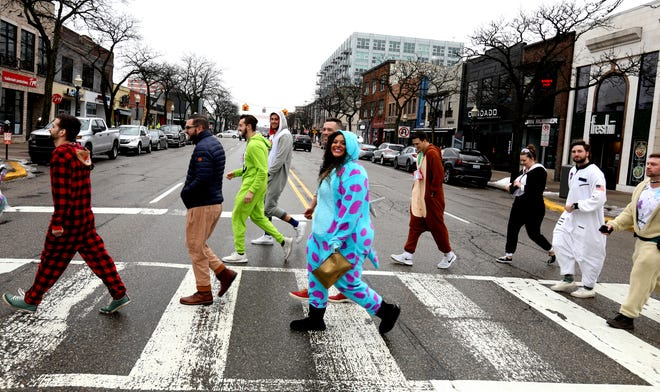 People cross Main Street in downtown Royal Oak heading from one bar to another during the fourth annual Onesie Bar Crawl at various bars in Royal Oak, Michigan on Saturday, January 25, 2020.