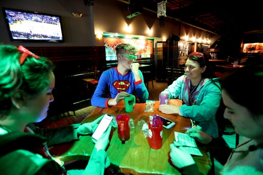 Friends in onesie outfits talk and drink inside Mr. B's Gastropub during the fourth annual Onesie Bar Crawl at various bars in Royal Oak, Michigan on Saturday, January 25, 2020.