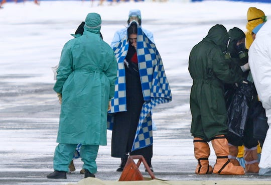 A group of medical personnel meet people, carried by a Russian military plane at an airport outside Tyumen, Russia, Wednesday, Feb. 5, 2020. Russia has evacuated 144 people, Russians and nationals of Belarus, Ukraine and Armenia, from the epicenter of the coronavirus outbreak in Wuhan, China.