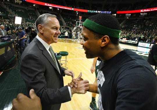 Newly retired Michigan State football coach Mark Dantonio is greeted warmly by Spartans star basketball player Cassius Winston on the court before MSU's game against Penn State Tuesday.