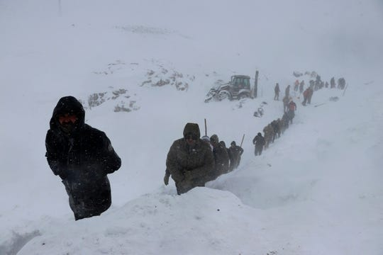 Emergency service members work in the snow around overturned vehicles, near the town of Bahcesehir, in Van province, eastern Turkey, Wednesday, Feb. 5, 2020.