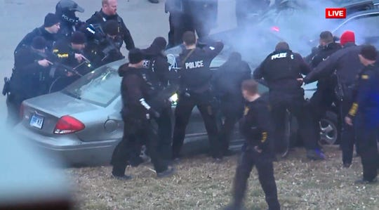 Law enforcement personnel surround a car after it was stopped as the driver approached the crowd near Union Station attending the Super Bowl parade and rally for the Kansas City Chief in Kansas City, Mo., Wednesday, Feb. 5, 2020. (FOXKC via AP)