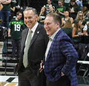 Retired football coach Mark Dantonio and basketball coach Tom Izzo meet on the court before MSU takes on Penn State.