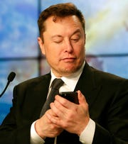 Elon Musk founder, CEO, and chief engineer/designer of SpaceX jokes with reporters as he pretends to be searching for an answer to a question on a cell phone during a news conference Jan. 19, 2020. Shares of the electric-vehicle maker fell 9.4% to $803.63, after rising as high as $968.99 Tuesday, Feb. 4, 2020, amid what looked like an unstoppable advance.