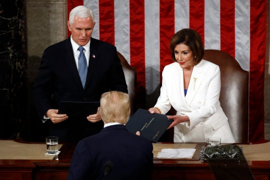 President Donald Trump hands copies of his speech to House Speaker Nancy Pelosi of Calif., and Vice President Mike Pence as he delivers his State of the Union address to a joint session of Congress on Capitol Hill in Washington, Tuesday, Feb. 4, 2020.
