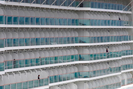 Passengers are seen on the World Dream cruise ship docked at Kai Tak cruise terminal in  Hong Kong, Wednesday, Feb. 5, 2020. A Hong Kong official says more than 3,600 people on board the cruise ship that was turned away from a Taiwanese port will be quarantined until they are checked for a new virus.